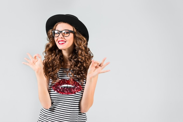 Szczęśliwa dziewczyna w okularach i kapeluszu na szarej ścianie