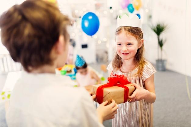Szczęśliwa Dziewczyna W Papierowej Koronie Bierze Prezent Darmowe Zdjęcia