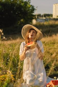 Szczęśliwa dziewczyna w parku na świeżym powietrzu z orzeźwiającym owocem arbuza kobieta zjada kawałek arbuza