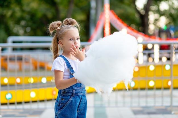 Szczęśliwa dziewczyna w parku rozrywki jedzenie waty cukrowej w lecie