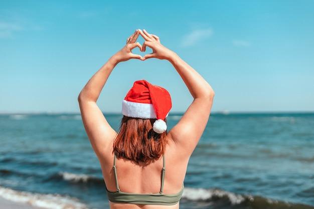Szczęśliwa dziewczyna w santa hat i stroju kąpielowym pokazując gest serca rękami, stojąc nad morzem
