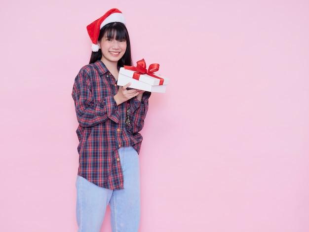 Szczęśliwa dziewczyna w santa hat otwierając pudełko przed różową ścianą
