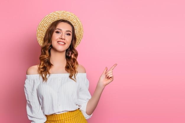 Szczęśliwa dziewczyna w słomkowym kapeluszu i białej sukience w stylu vintage uśmiecha się i wskazuje palcem. dziewczyna w letnie ubrania odizolowane na różowej ścianie młoda kobieta pokazuje kciuk do góry