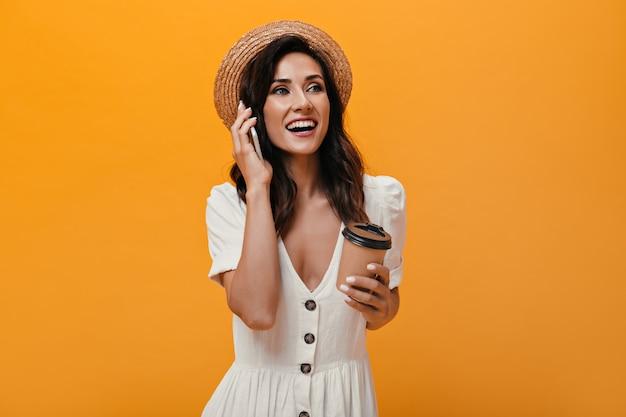 Szczęśliwa dziewczyna w słomkowym kapeluszu rozmawia przez telefon i trzyma szklankę kawy. piękna pani w jasne ubrania trzyma smartfon i herbatę na na białym tle.