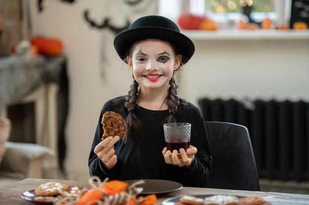 Szczęśliwa dziewczyna w stroju halloween mająca ciastko i napój