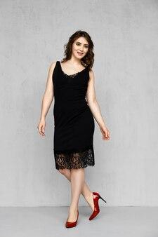 Szczęśliwa dziewczyna w sukience z koronkowym obszyciem i pozowanie w paski