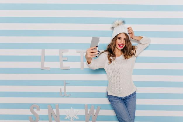Szczęśliwa dziewczyna w świetnym nastroju chytrze patrząc, uśmiechając się i pozując z nowym telefonem