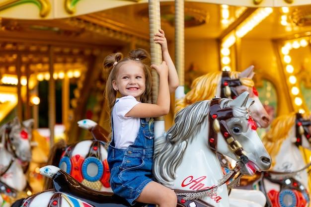 Szczęśliwa dziewczyna w wesołym miasteczku jeździ latem na koniu na karuzeli