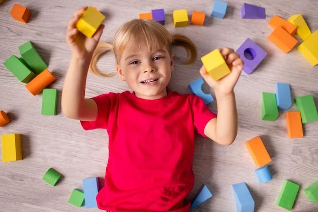 Szczęśliwa dziewczyna w wieku przedszkolnym gra z kostkami kolorowe plastikowe zabawki. widok z góry z góry.