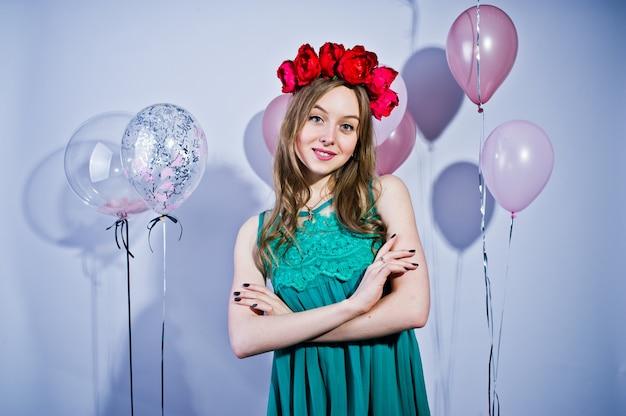 Szczęśliwa dziewczyna w zielonej turkusowej sukni i wianku z barwionymi balonami odizolowywającymi na bielu. świętujemy urodziny.