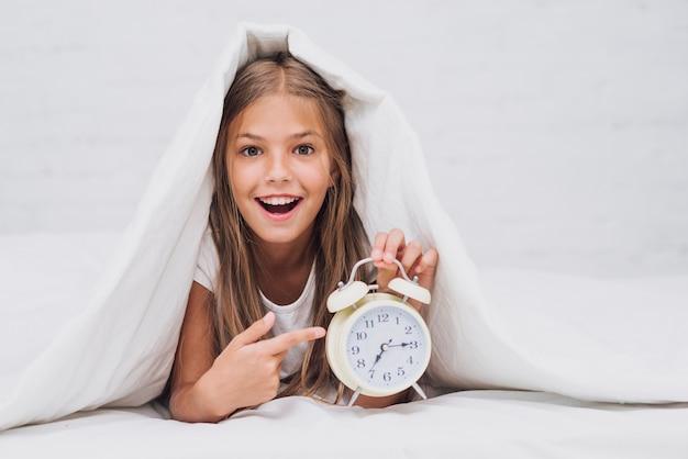 Szczęśliwa dziewczyna wskazuje przy zegarem