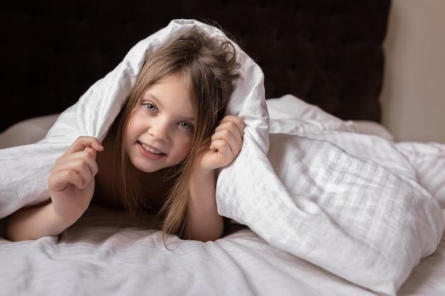 Szczęśliwa dziewczyna wygląda spod koca na łóżku w domu