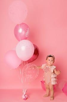 Szczęśliwa dziewczyna z balonami na różowym tle obchodzi swoje pierwsze urodziny