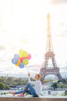 Szczęśliwa dziewczyna z bukietem kolorowych balonów w paryżu, w pobliżu wieży eiffla.