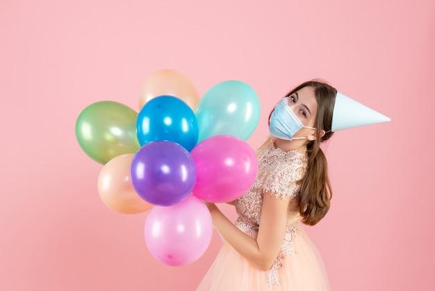 Szczęśliwa dziewczyna z czapką i maską medyczną trzymając kolorowe balony na różowo