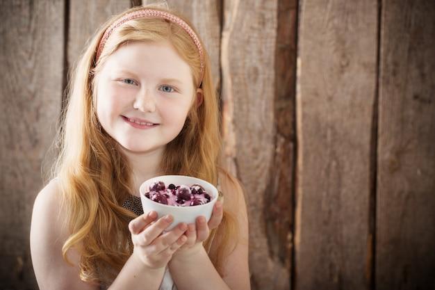 Szczęśliwa dziewczyna z deserem na drewnianym tle