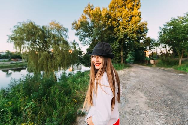 Szczęśliwa dziewczyna z długimi włosami i kapeluszem na głowie szczerze się uśmiecha i patrzy przez ramię