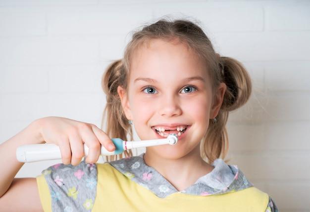 Szczęśliwa dziewczyna z elektryczną szczoteczką do zębów myje zęby i uśmiecha się