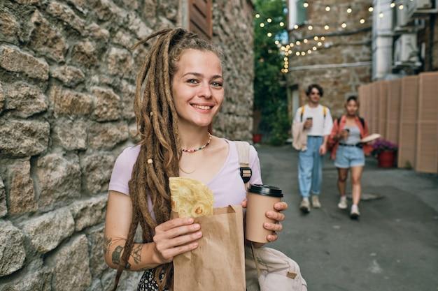 Szczęśliwa dziewczyna z fastfoodem stojąca przy kamiennym budynku