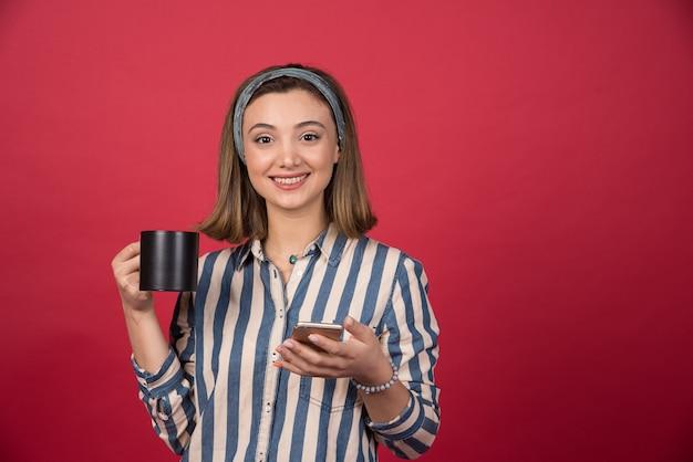 Szczęśliwa dziewczyna z filiżanką herbaty trzymając telefon komórkowy