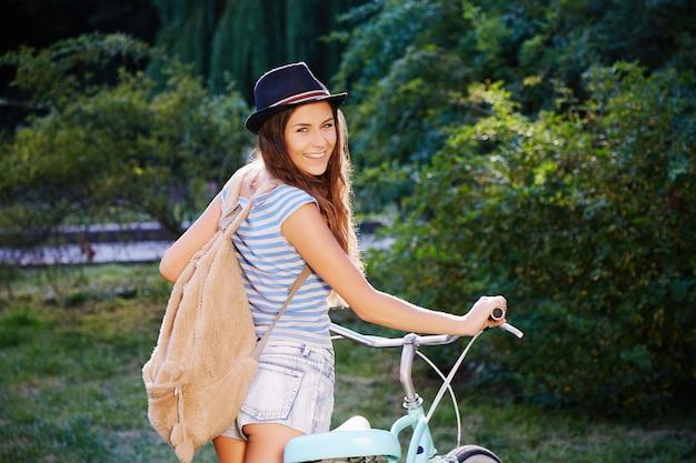 Szczęśliwa dziewczyna z kręconymi włosami na sobie kapelusz, top i spodenki stojąc z rowerem w parku, podróżując, portret, uśmiechając się.