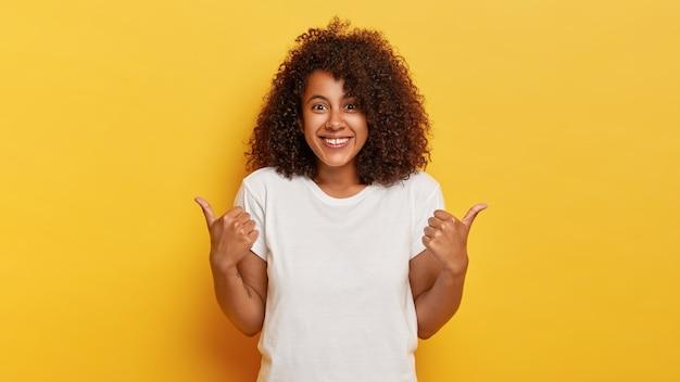 Szczęśliwa dziewczyna z kręconymi włosami pokazuje kciuki w górę, okazuje komuś wsparcie i szacunek, uśmiecha się przyjemnie, osiąga pożądany cel, nosi białą koszulkę, odizolowaną na żółtej ścianie
