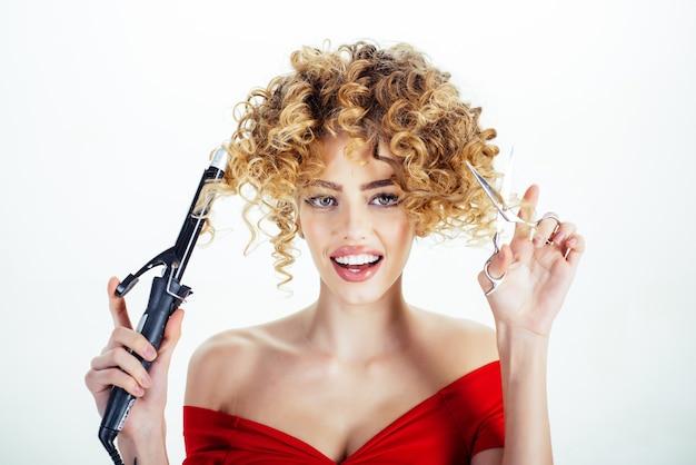 Szczęśliwa dziewczyna z kręconymi włosami trzyma sprzęt fryzjerski fryzjer przemysł kosmetyczny zawód makijaż