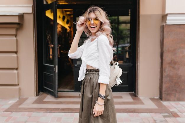 Szczęśliwa dziewczyna z modną kręconą fryzurą, śmiejąc się i trzymając żółte okulary przeciwsłoneczne, pozując przed sklepem