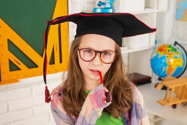 Szczęśliwa dziewczyna z piórem w ustach w czapce ukończenia szkoły w pobliżu tablicy szkolnej