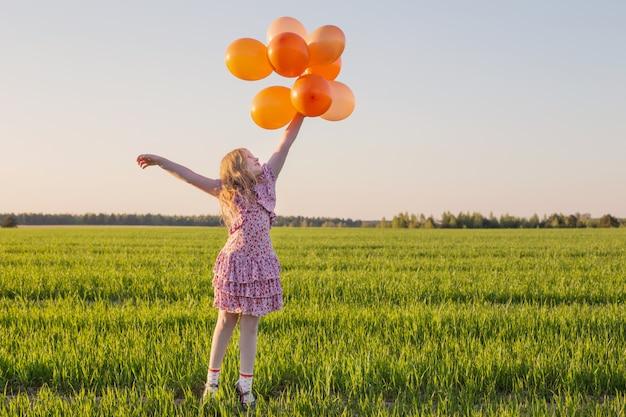 Szczęśliwa dziewczyna z pomarańczowymi balonami plenerowymi