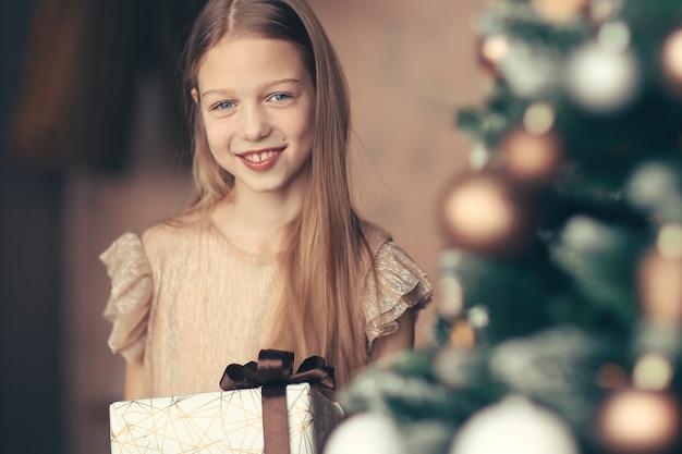 Szczęśliwa dziewczyna z prezentem świątecznym stojąca w pobliżu choinki