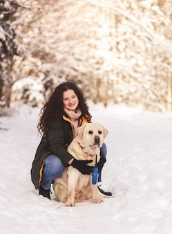 Szczęśliwa dziewczyna z psem labrador w zimowym lesie