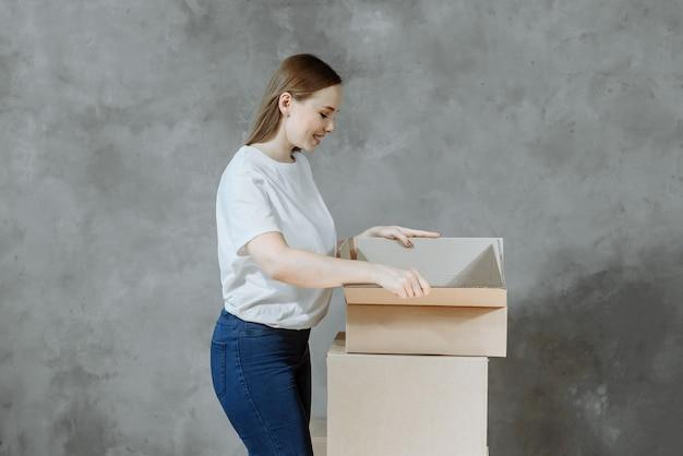 Szczęśliwa dziewczyna z pudełkami do przeprowadzki w nowym mieszkaniu.