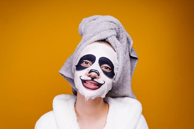 Szczęśliwa dziewczyna z ręcznikiem na głowie uśmiechnięta, na masce z pyskiem pandy
