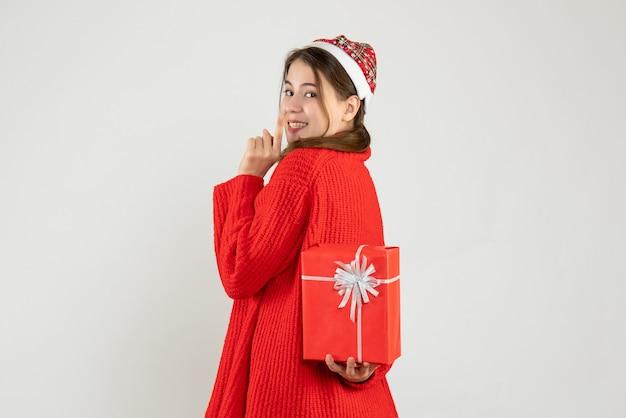 Szczęśliwa dziewczyna z santa hat chowając świąteczny prezent za plecami na białym tle