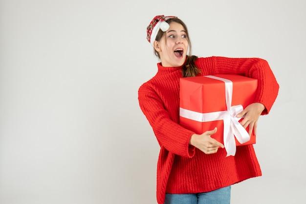 Szczęśliwa dziewczyna z santa hat palcem wskazującym coś gospodarstwa prezent na białym tle