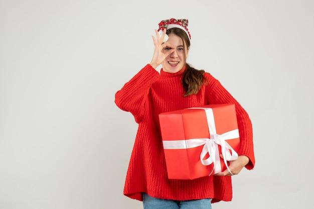 Szczęśliwa dziewczyna z santa hat stawiając znak okey przed jej okiem trzymając prezent na białym tle