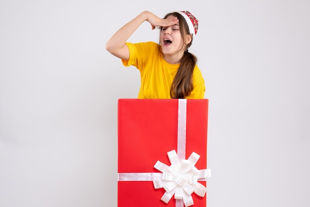 Szczęśliwa dziewczyna z santa hat stojącego za wielkim prezentem na białym boże narodzenie