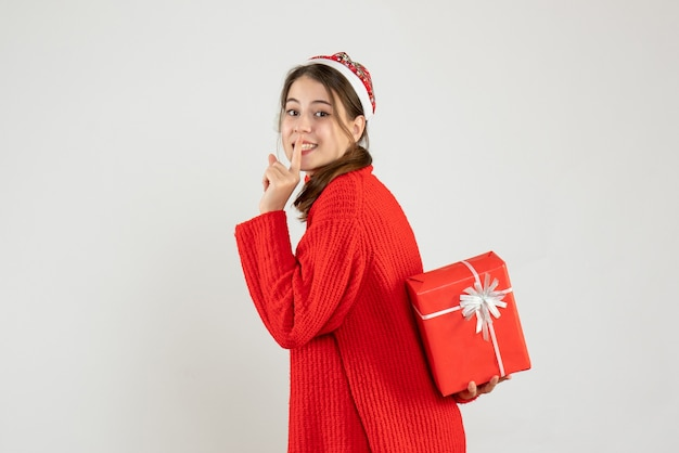 Szczęśliwa dziewczyna z santa hat trzyma jej prezent świąteczny, dzięki czemu znak shh na białym tle