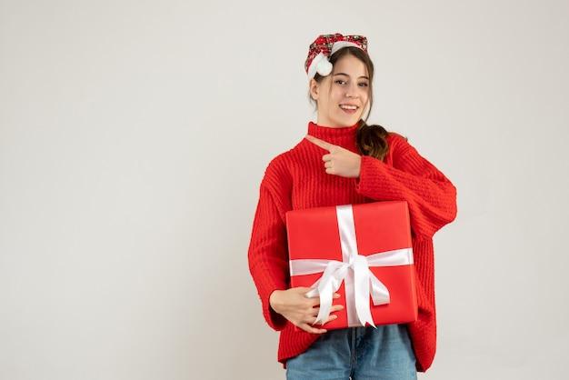 Szczęśliwa dziewczyna z santa hat trzyma obecny palec wskazujący coś stojącego na białym
