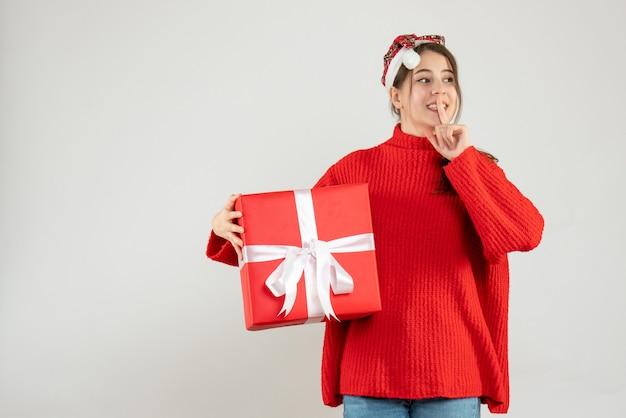 Szczęśliwa dziewczyna z santa hat trzyma prezent, co znak shh na białym tle