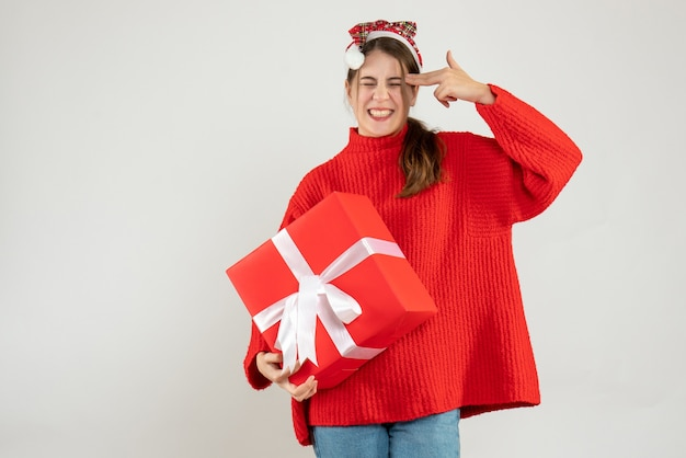 Szczęśliwa dziewczyna z santa hat trzyma prezent na umieszczenie pistoletu palcowego w jej świątyni biały