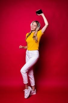 Szczęśliwa dziewczyna z, słuchanie muzyki w słuchawkach i taniec, trzymając smartfon. na czerwonej ścianie.