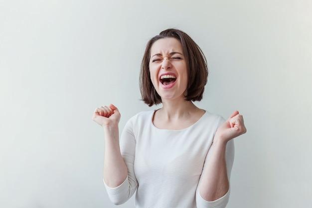 Szczęśliwa dziewczyna z uśmiechem. piękno portret młodej szczęśliwej pozytywnej roześmianej brunetki kobiety na białym na białym tle