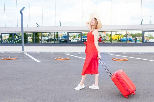 Szczęśliwa dziewczyna z walizką na lotnisku w czerwonej sukience i kapeluszu jedzie latem na wycieczkę lub wakacje