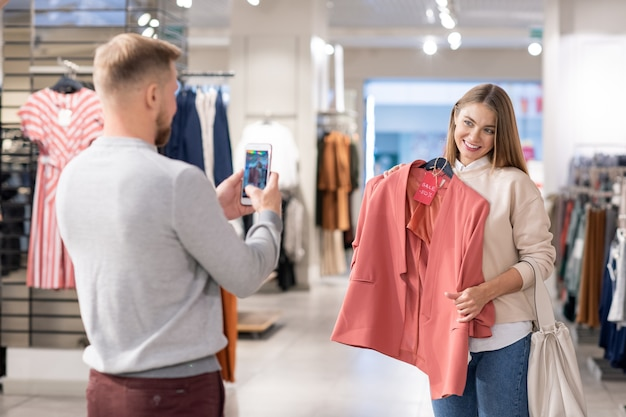 Szczęśliwa dziewczyna z zębatym uśmiechem trzymając różową kurtkę przy klatce piersiowej, stojąc przed młodym mężczyzną fotografującym ją na smartfonie