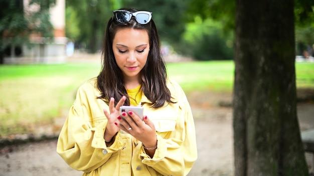 Szczęśliwa dziewczyna za pomocą inteligentnego telefonu latem w parku
