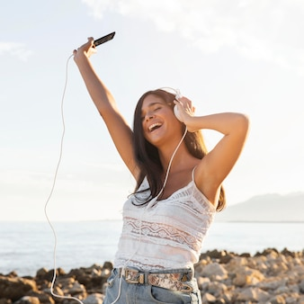 Szczęśliwa dziewczyna ze słuchawkami na plaży