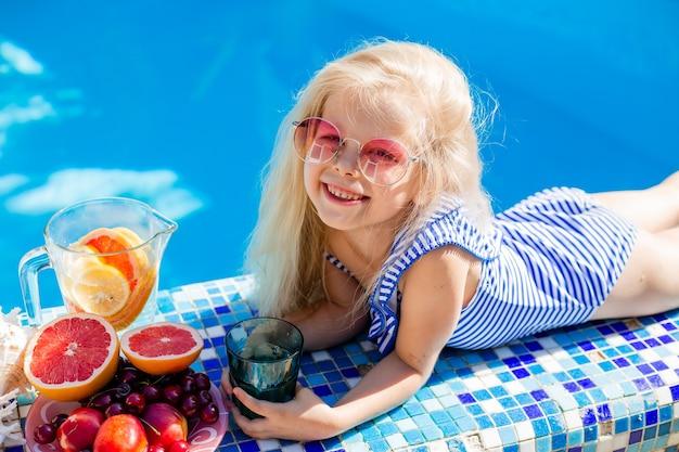 Szczęśliwa dziewczyna zjada owoce latem przy basenie