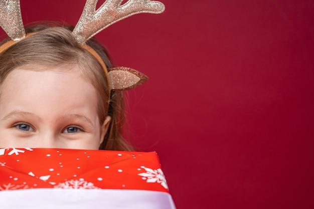 Szczęśliwa dziewczynka 4 lata w poroża renifera na jaskrawoczerwonym.